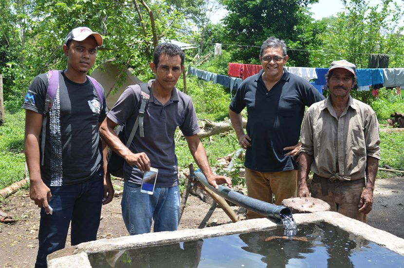 Farmer and technicians watch water pushed solar pump coming into tank