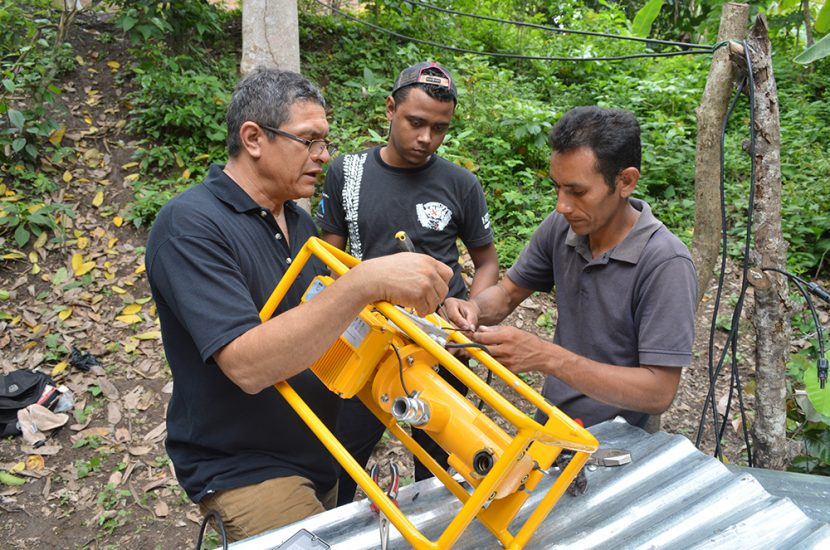 Water pump with Technical Coordinator on left & youth technicians on right