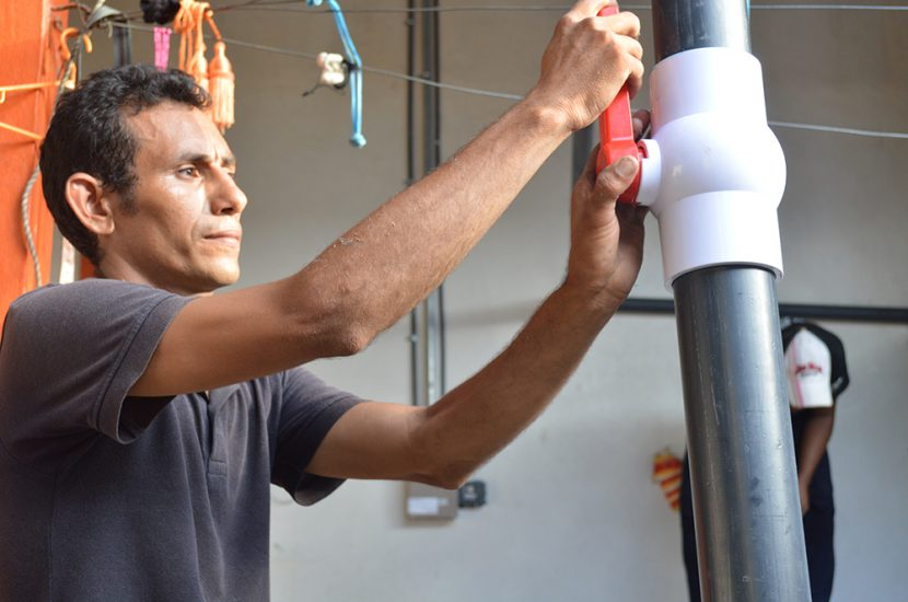 Youth technician adjusting water purification & pumping system